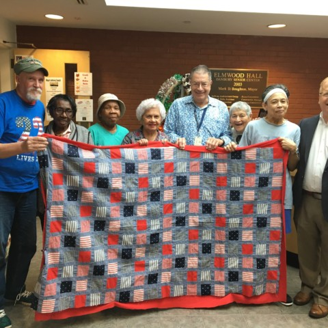 Mayor Mark posing with seniors at Elmwood Hall showing off one of the quilts on sale for the Craft and Bake Sale